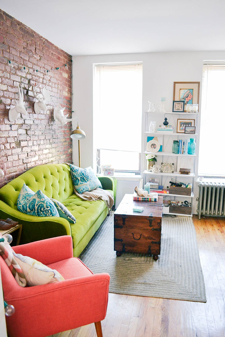 top 10 popular posts of 2015 from Advicefroma20Something.com, boho living room, nyc apartment tour, colorful living room, colorful decor ideas, green couch, velvet couch, animal heads, wooden trunk coffee table