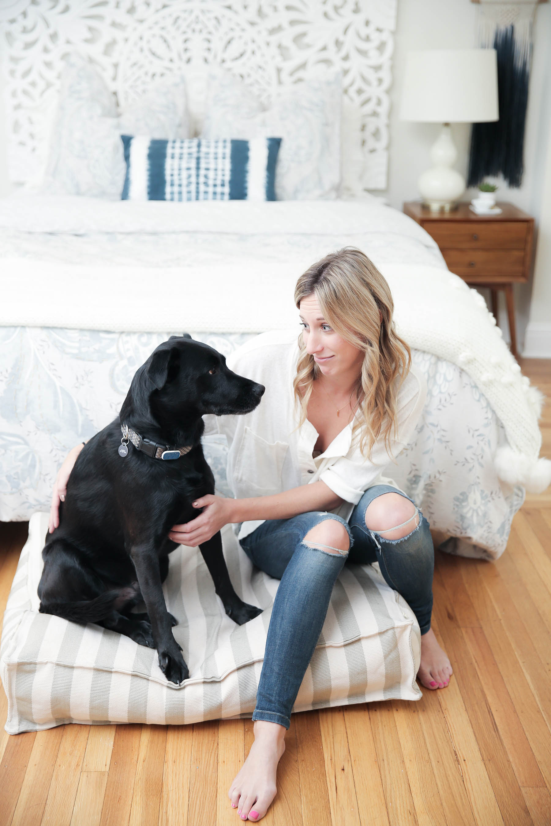 Amanda Holstein with her black lab dog Auggie in stylish boho bedroom