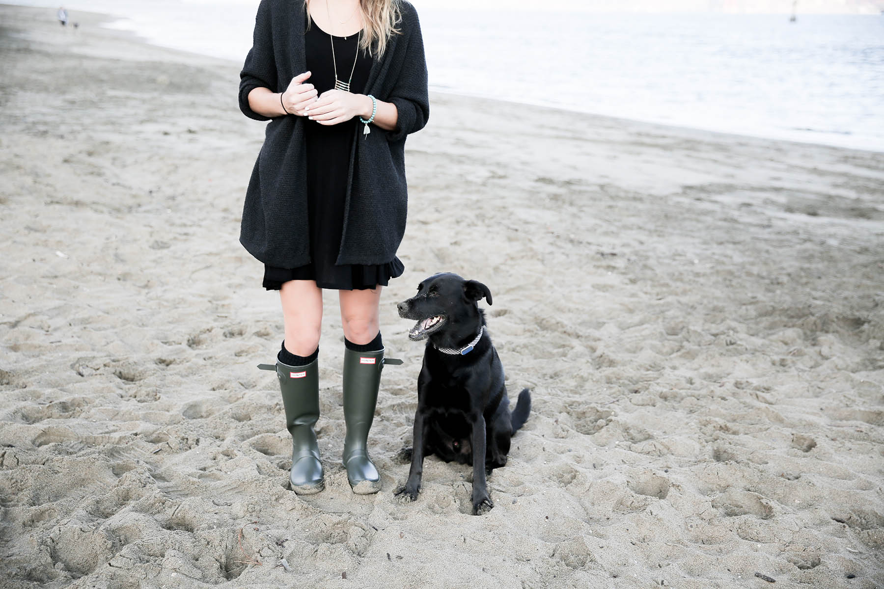 black lab on the beach with Amanda Holstein in hunter boots