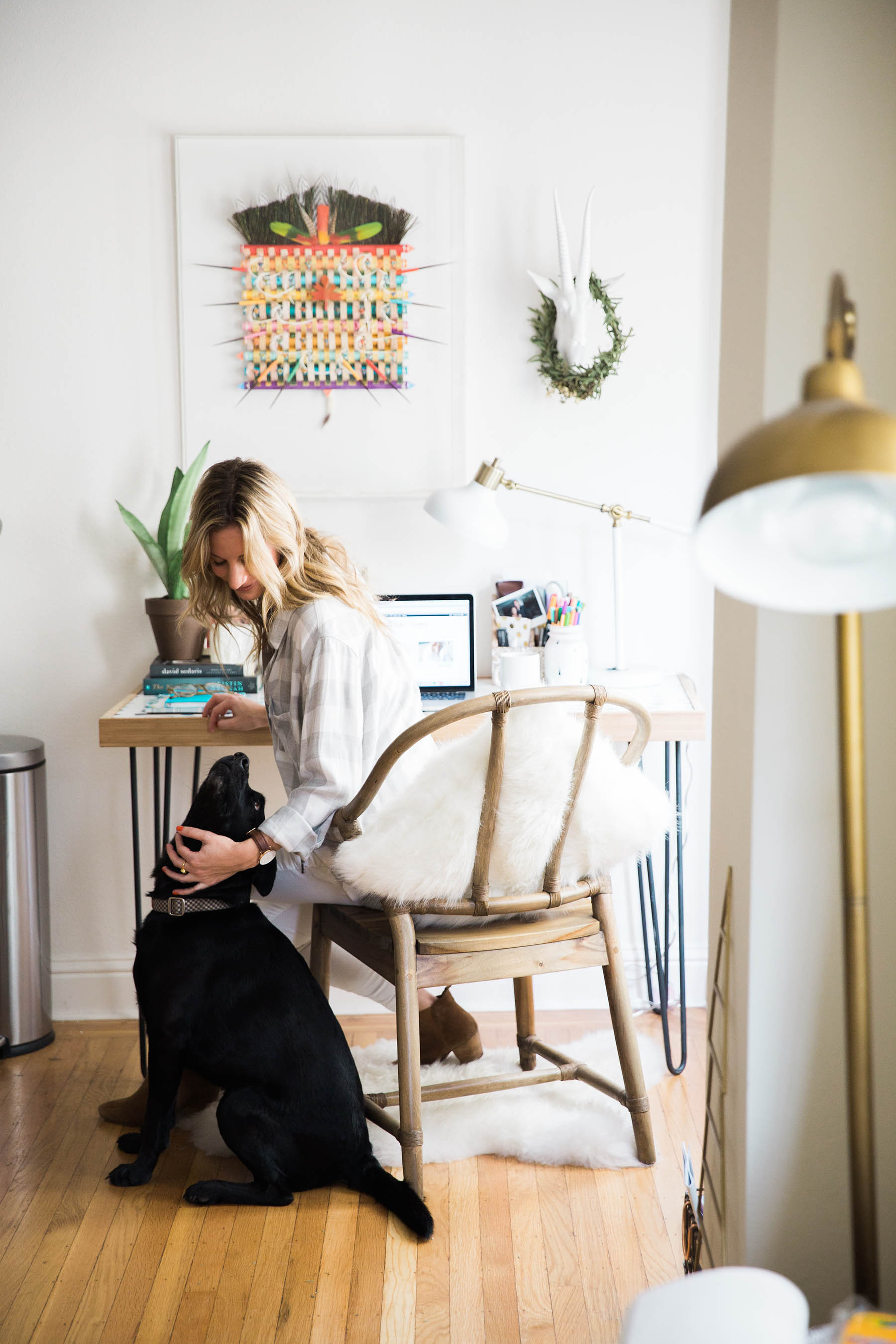 Amanda Holstein blogging at her boho style desk with her black lab