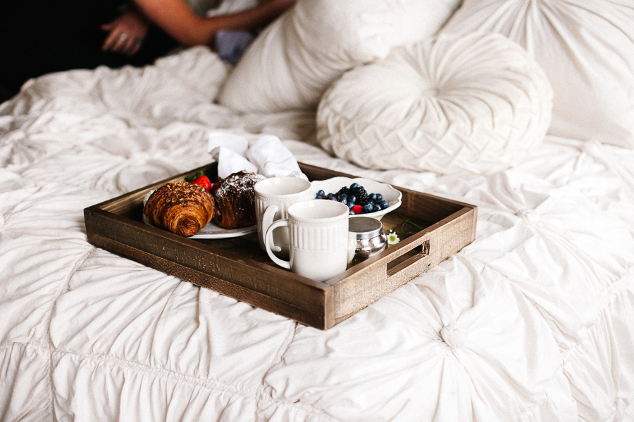 Breakfast in bed on wooden tray with white duvet by Mary Claire Photography