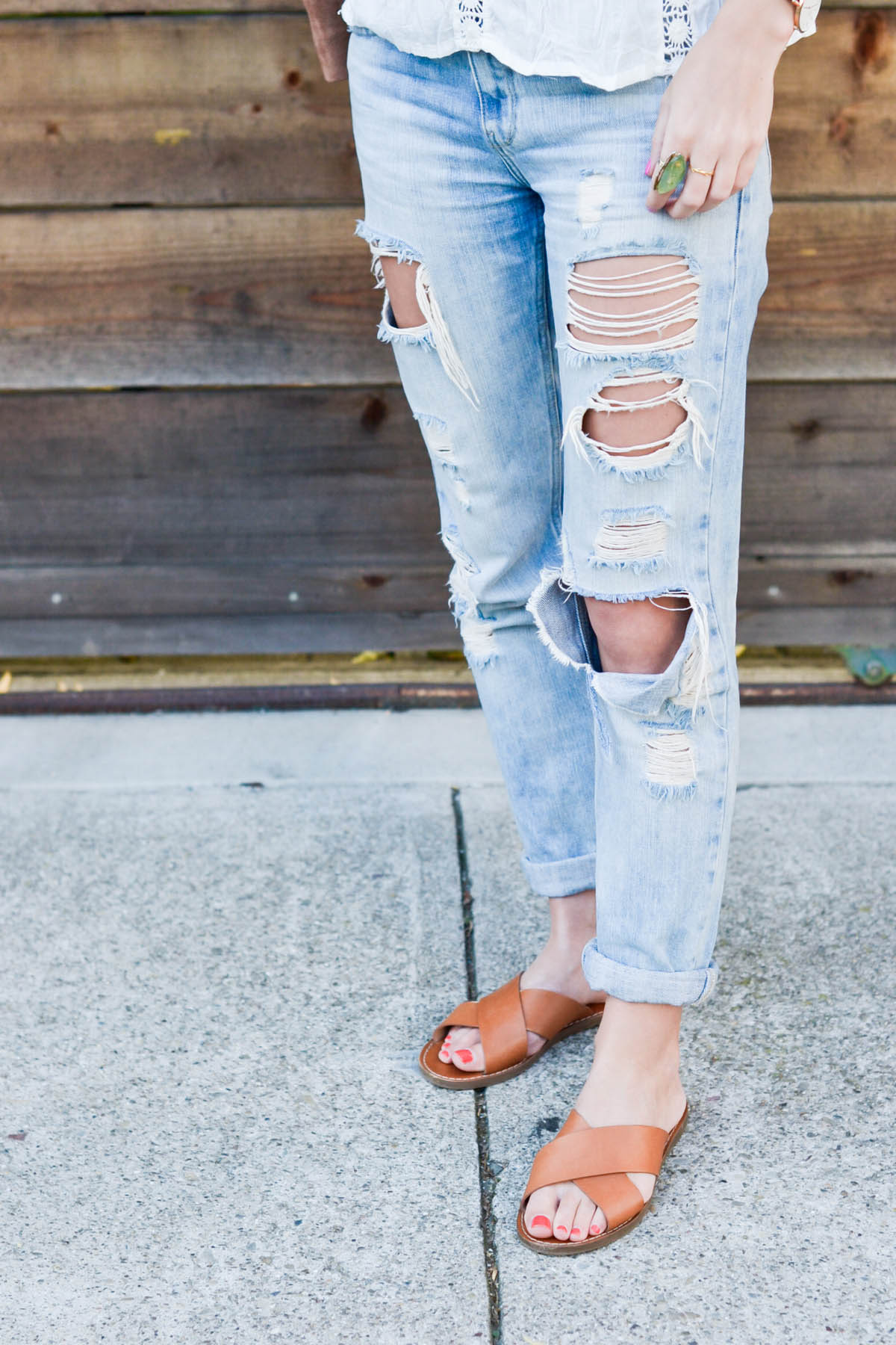Amanda Holstein in ripped boyfriend jeans and madewell slides brown leather sandals