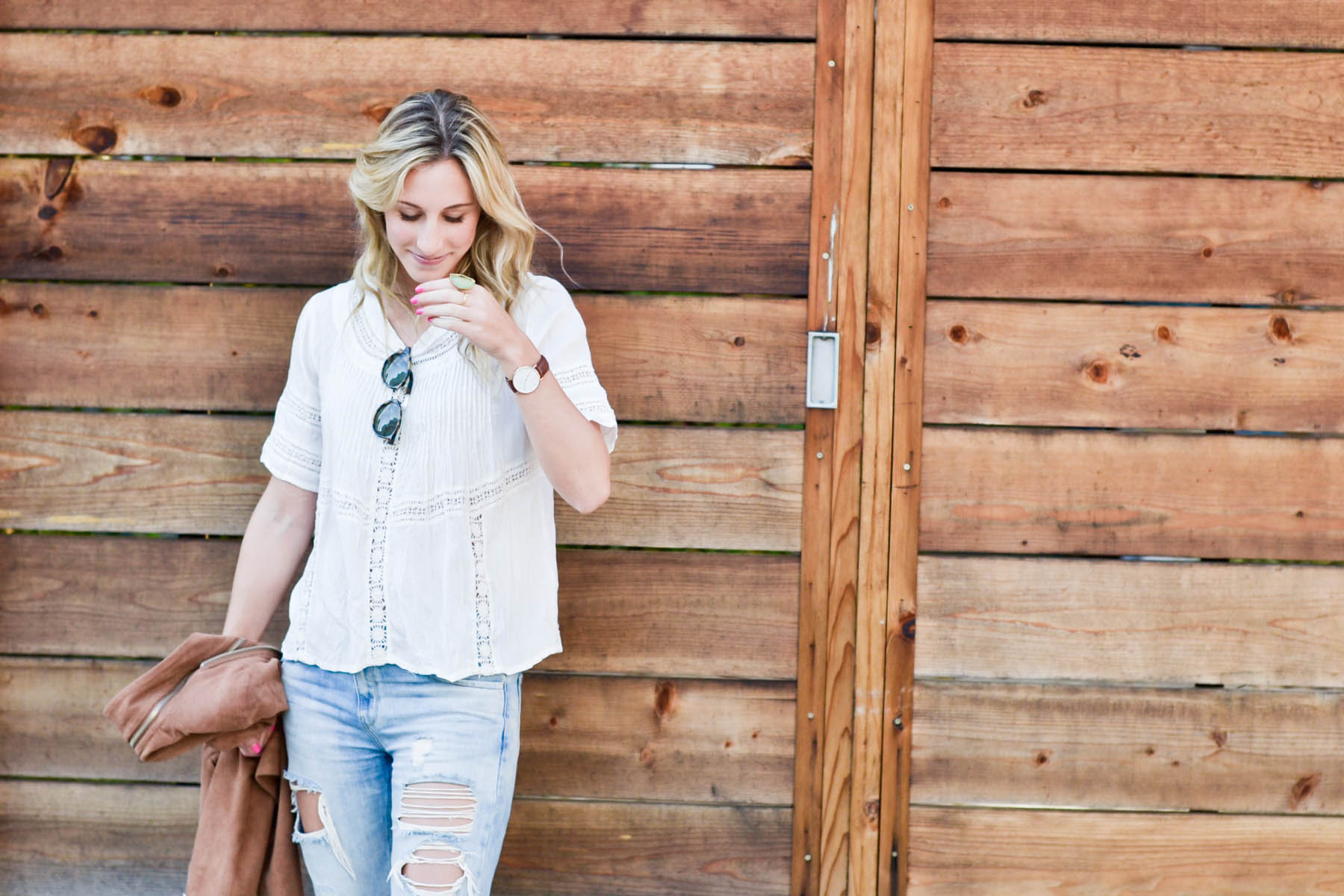 Amanda Holstein in revolve clothing white lace top, madewell sunglasses, brown suede moto jacket, ripped boyfriend jeans, distressed denim