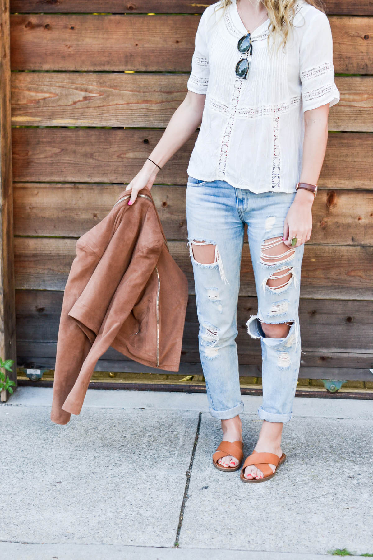 Amanda Holstein in revolve clothing white lace top, madewell sunglasses, brown suede moto jacket, ripped boyfriend jeans, distressed denim, and madewell slides brown leather sandals