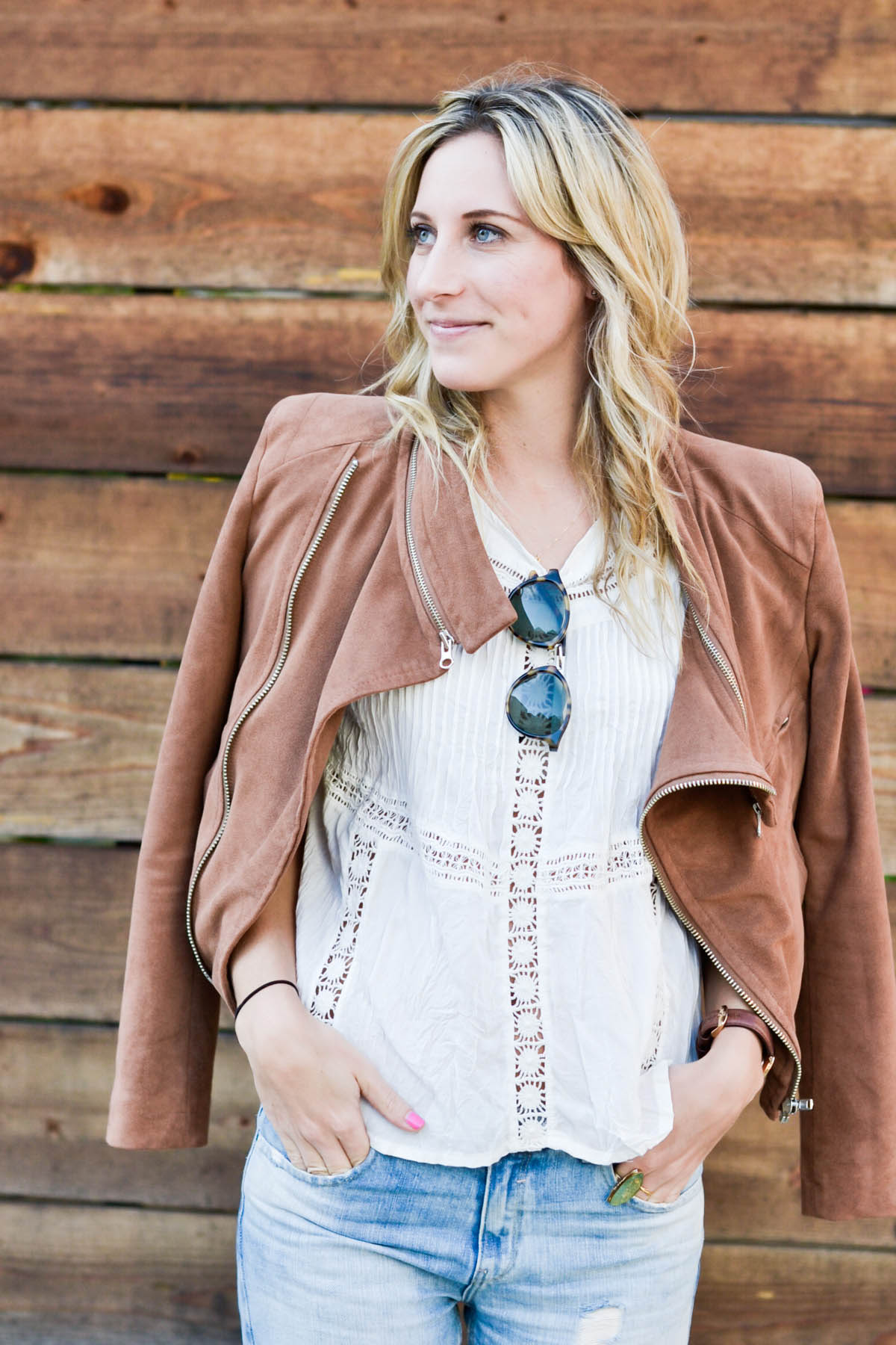 Amanda Holstein in revolve clothing white lace top, madewell sunglasses, brown suede moto jacket