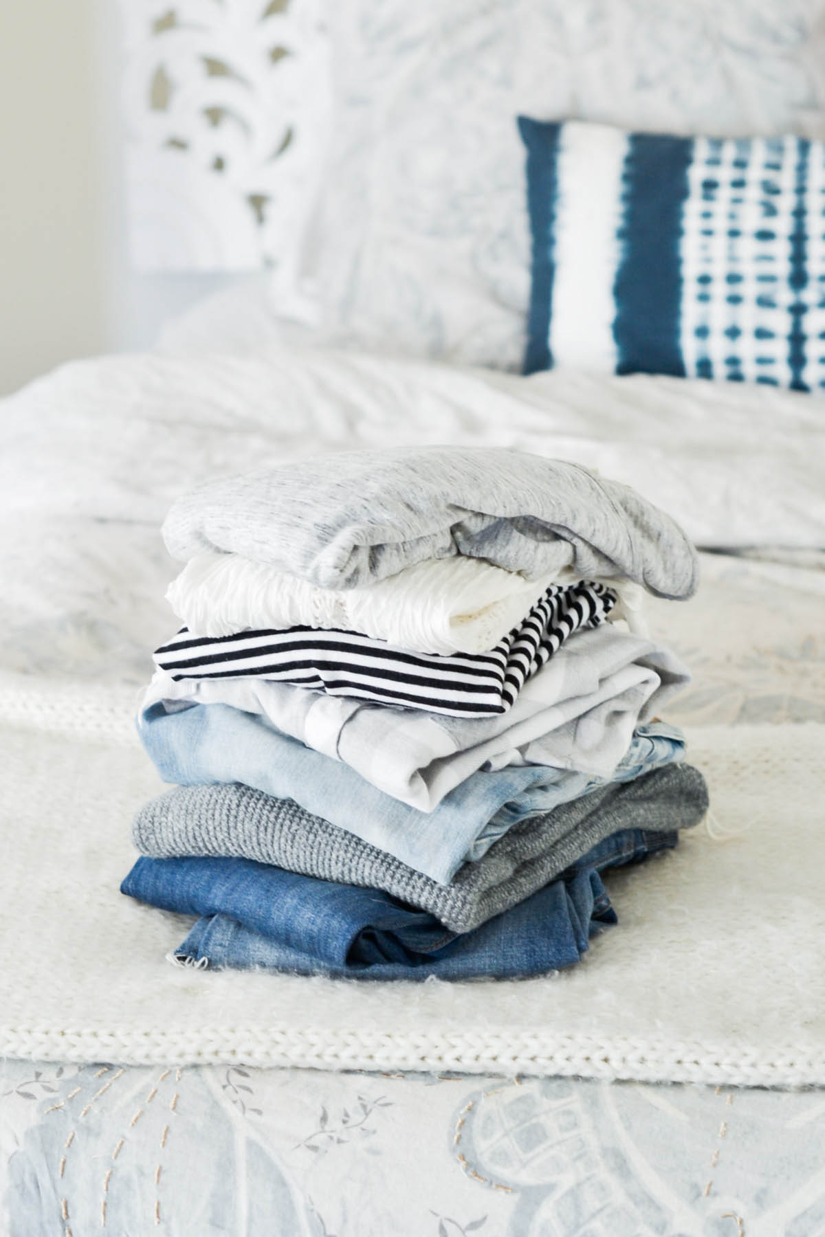 pile of clothes for capsule wardrobe including neutrals and basics
