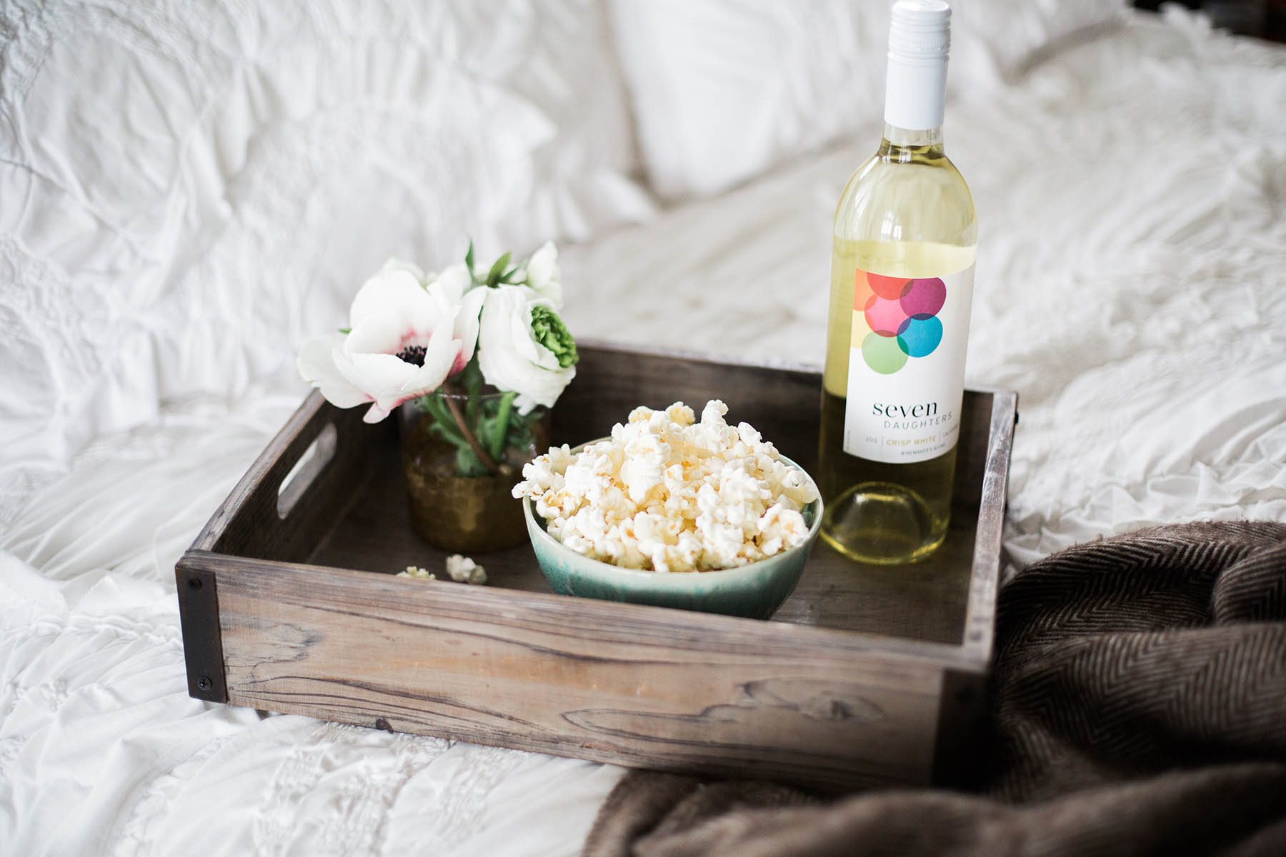 tray of popcorn and seven daughters wine on bed for movie night