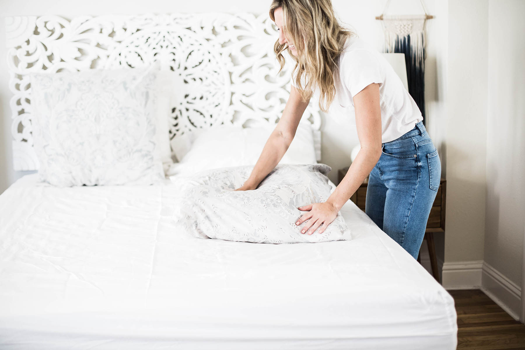 Amanda Holstein making the bed with Anthropologie bedding and Cocoon by Sealy mattress