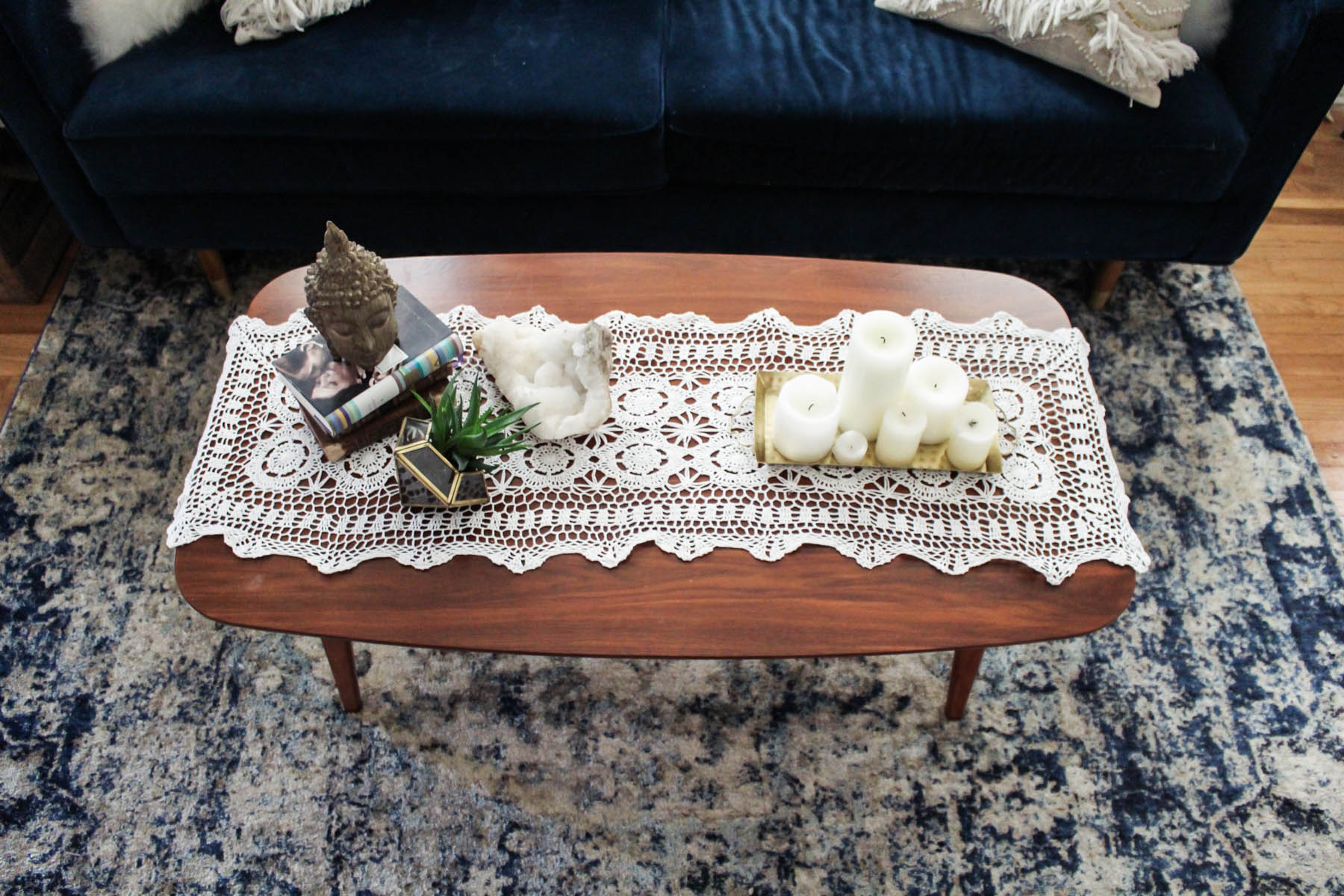 boho coffee table decor with crochet runner, candles, and Lulu & Georgia rug
