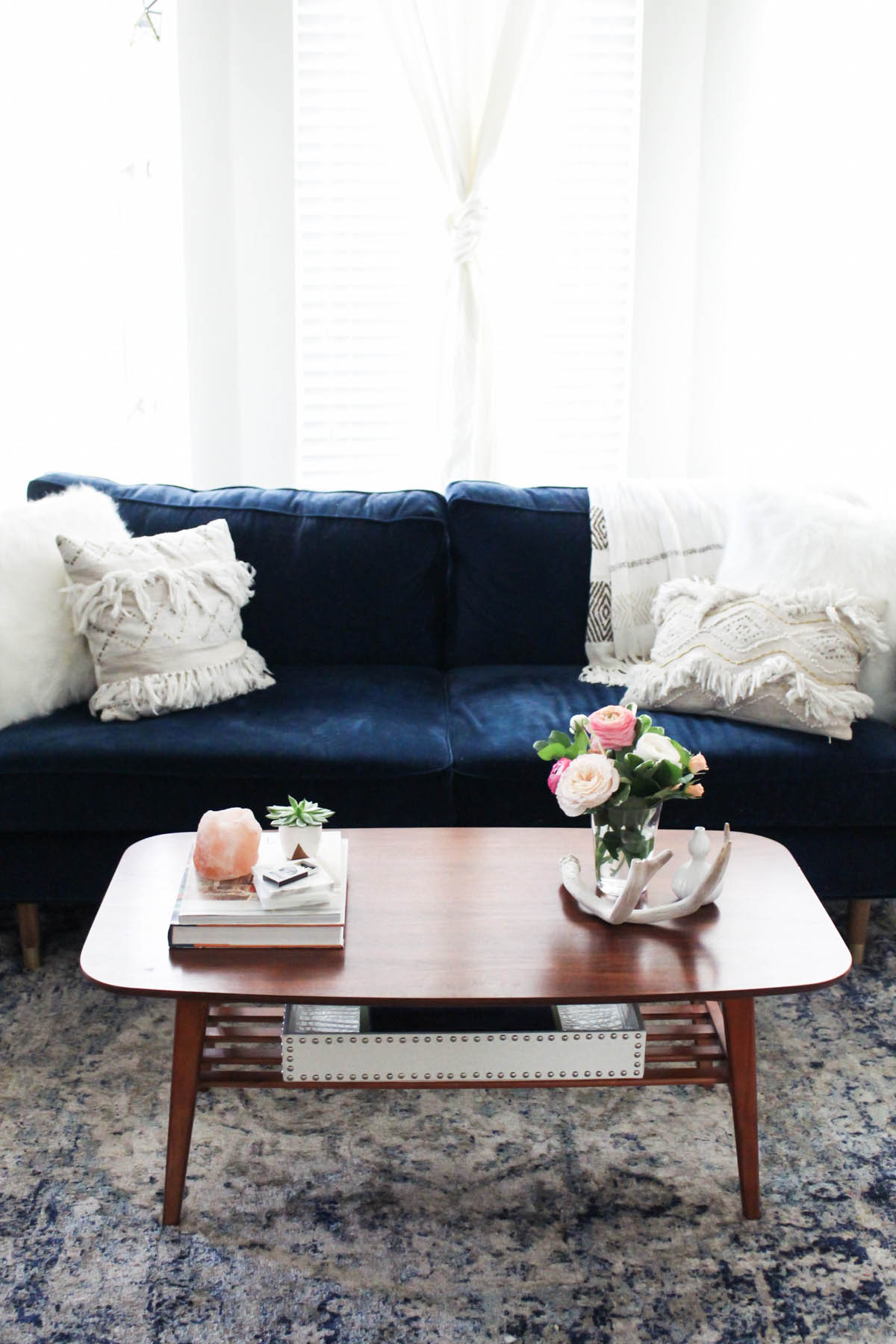 Urban Outfitters coffee table with navy couch in feminine living room