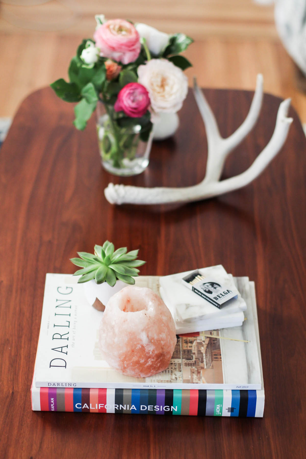 feminine coffee table styling with flowers, antlers, and geodes
