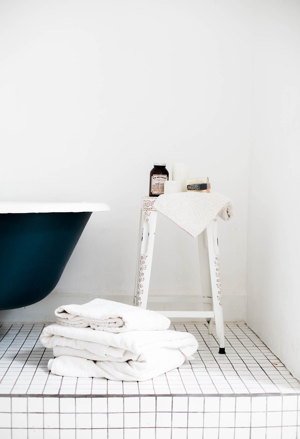 white bathroom with clawfoot tub and stool