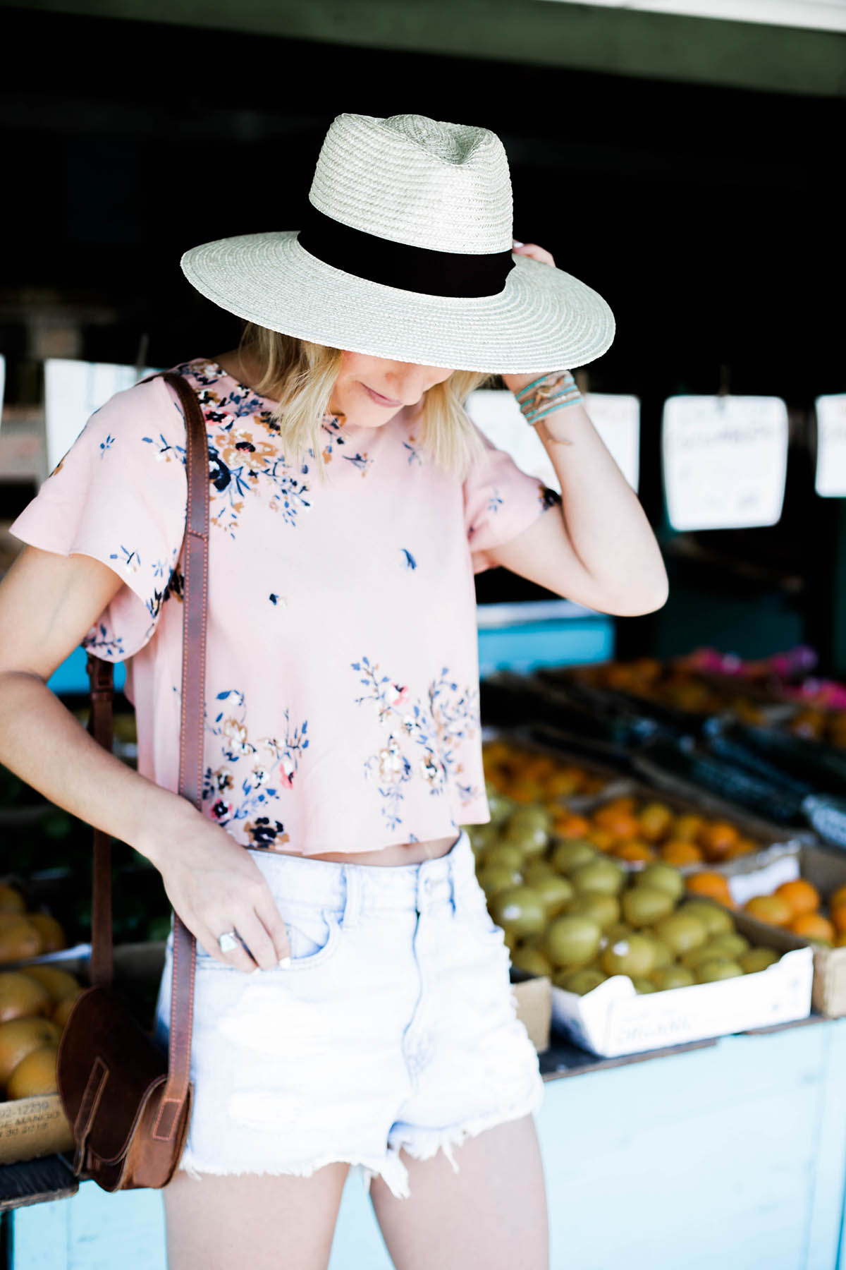 Amanda Holstein in Urban Outfitters crop top, panama hat, and denim shorts