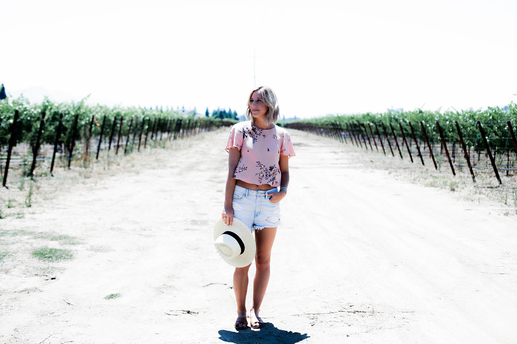 Amanda Holstein in Urban Outfitters crop top, panama hat, and denim shorts at Napa vineyard
