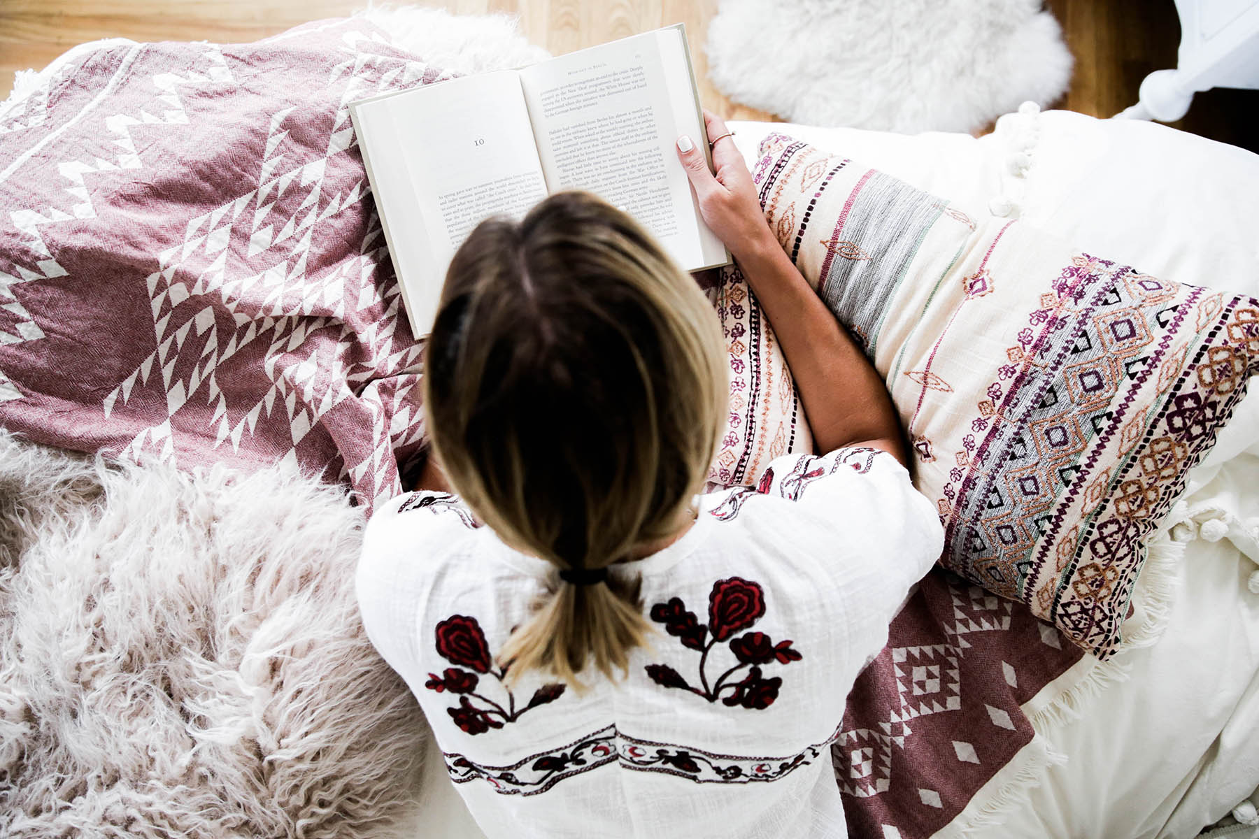 Amanda Holstein reading in bed with Urban Outfitters Urban Outfitters bedroom with Magical Thinking Pom-Fringe Duvet Cover and Agda Printed Yarn Pillow