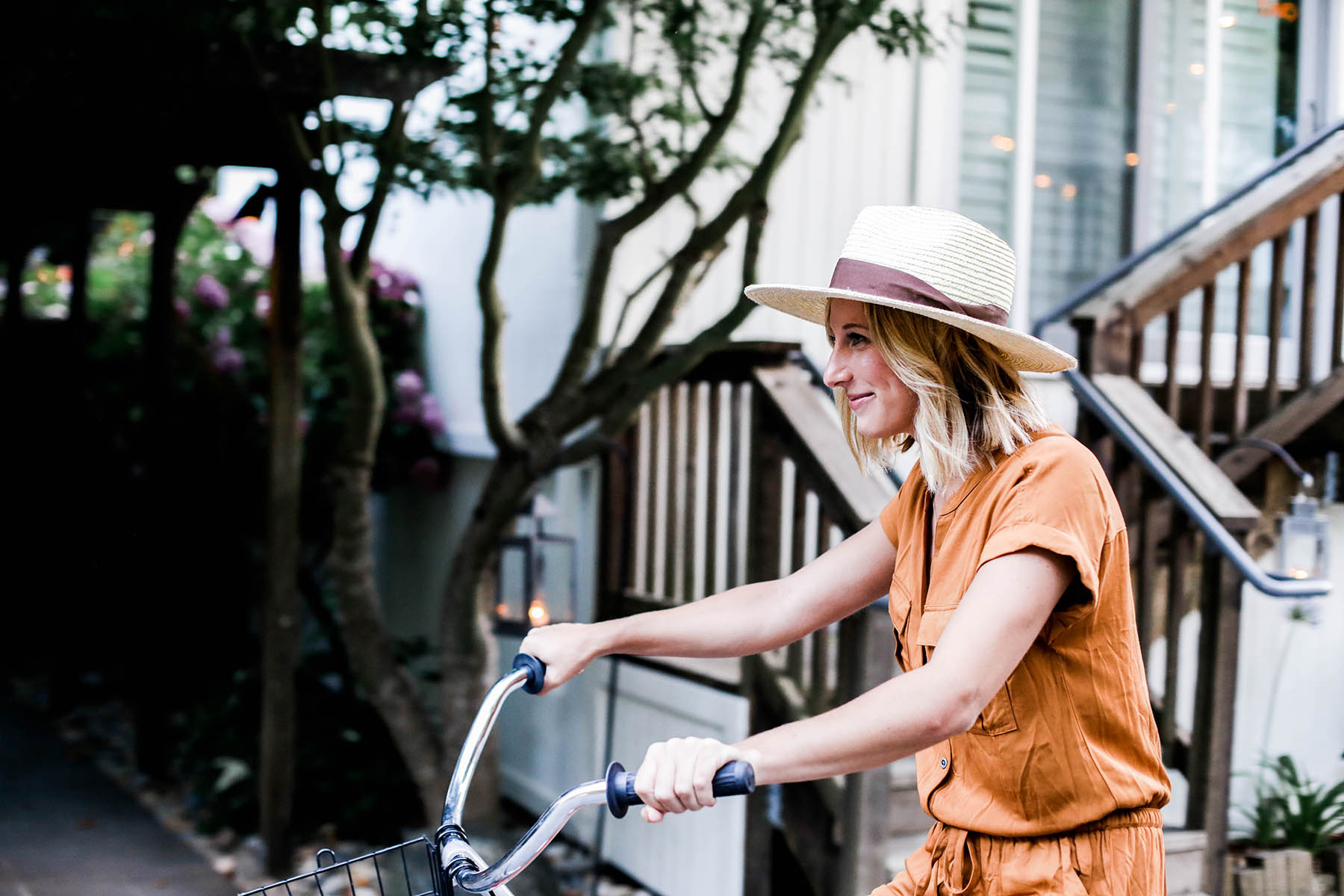 Amanda Holstein riding bikes in Old Navy romper and woven fedora hat
