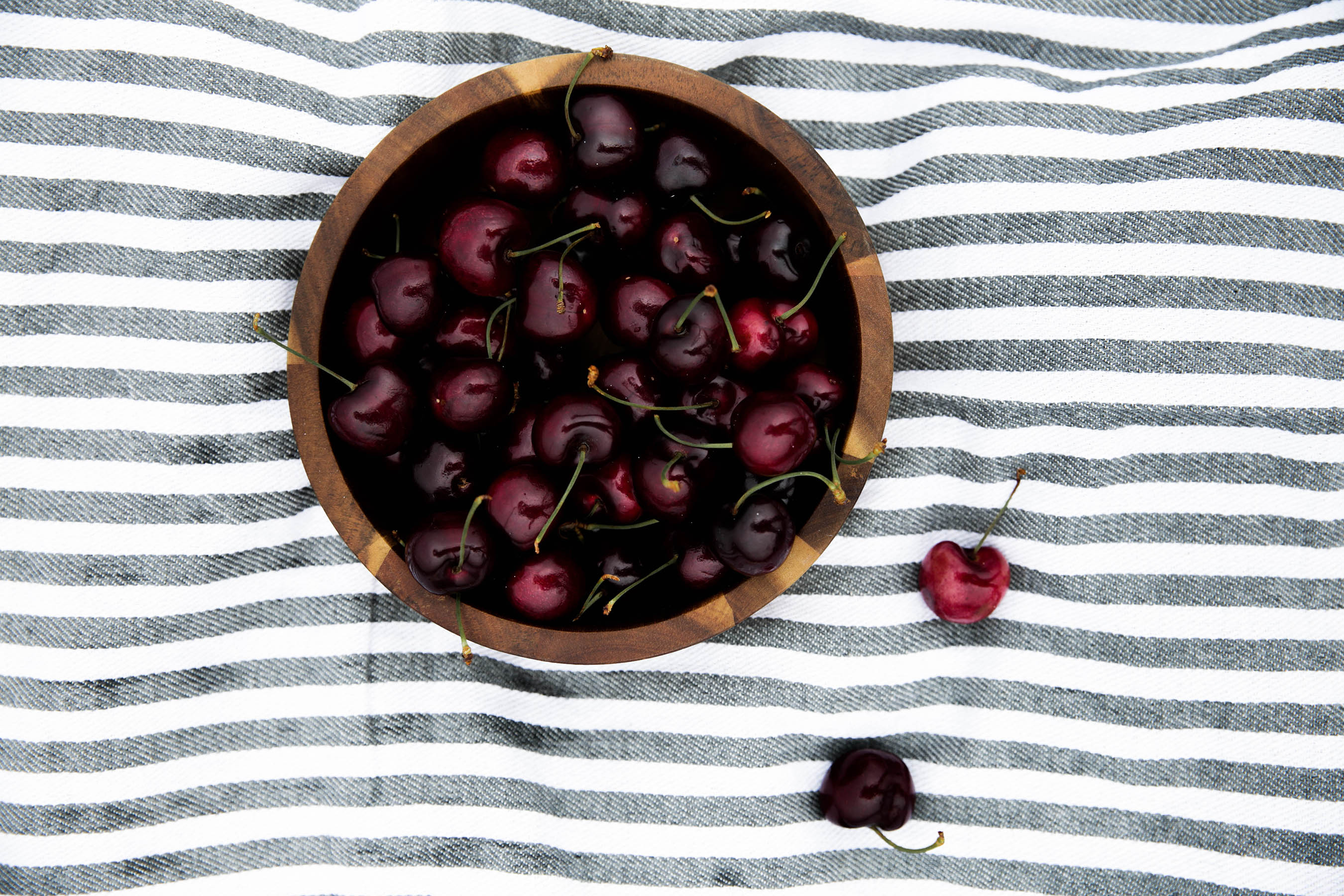 bowl of cherries on striped blanket for summer picnic