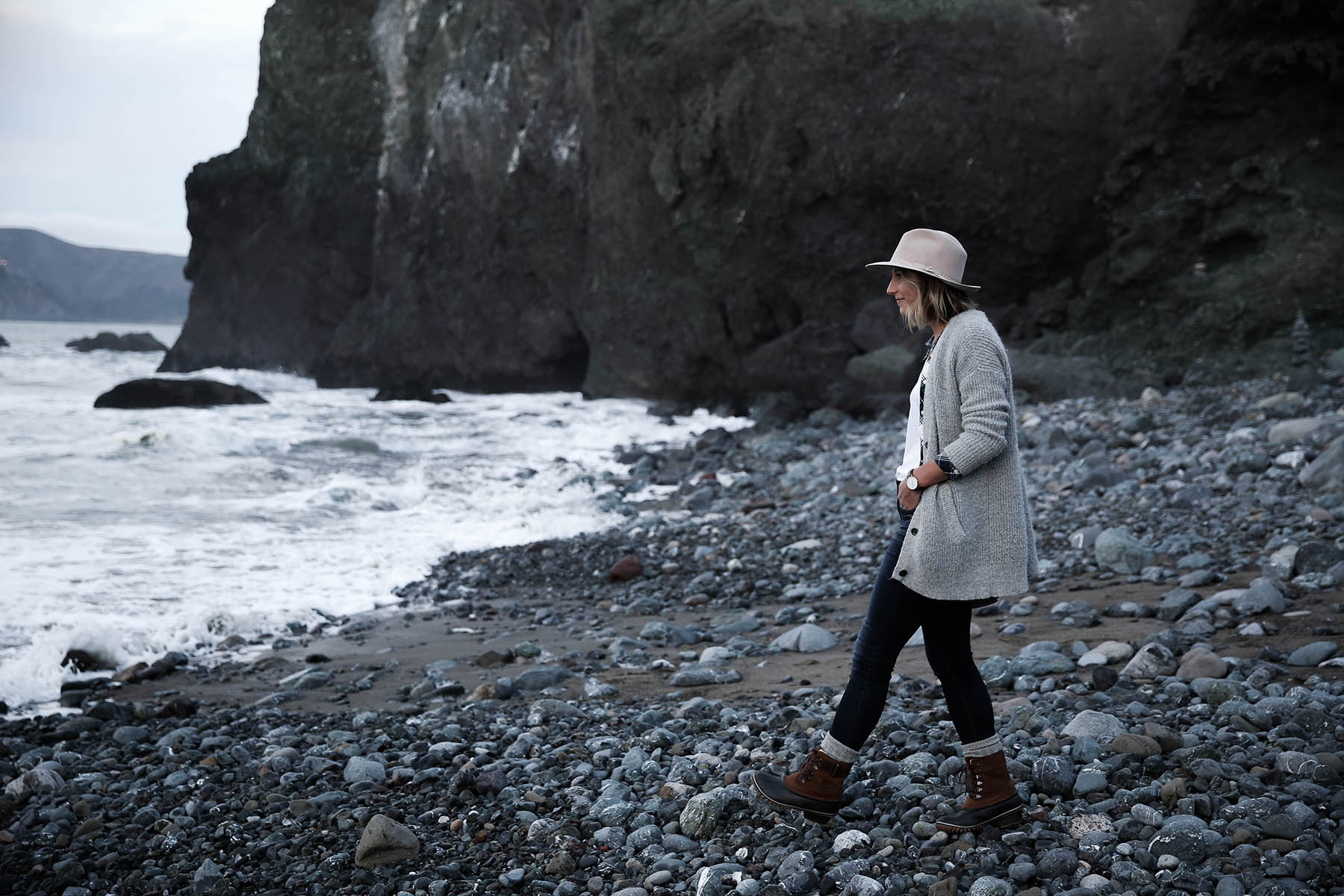 san francisco hikes on beach in sorel boots and grey cardigan