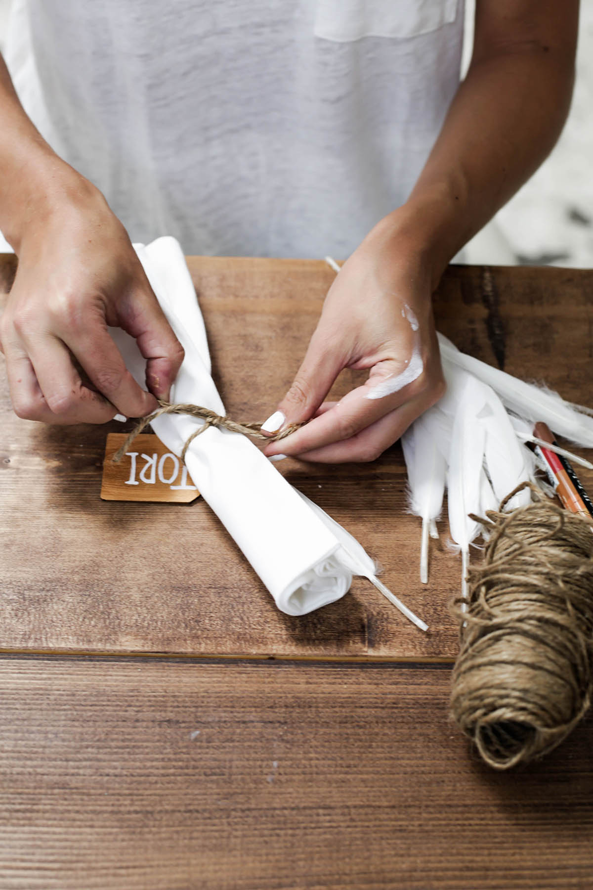 DIY name tag table setting with twine and feathers and white napkins
