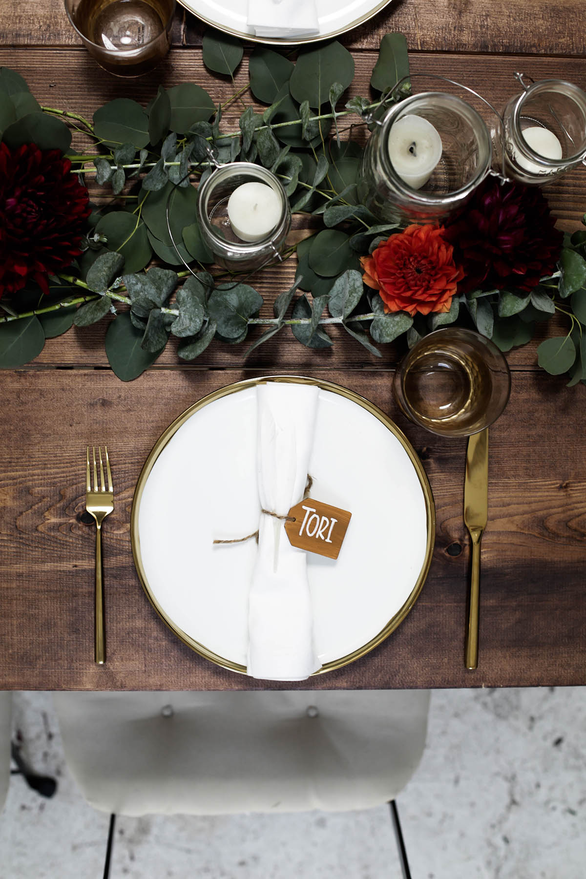 natural bohemian holiday tablescape with gold flatware, candles, mason jars, florals and eucalyptus