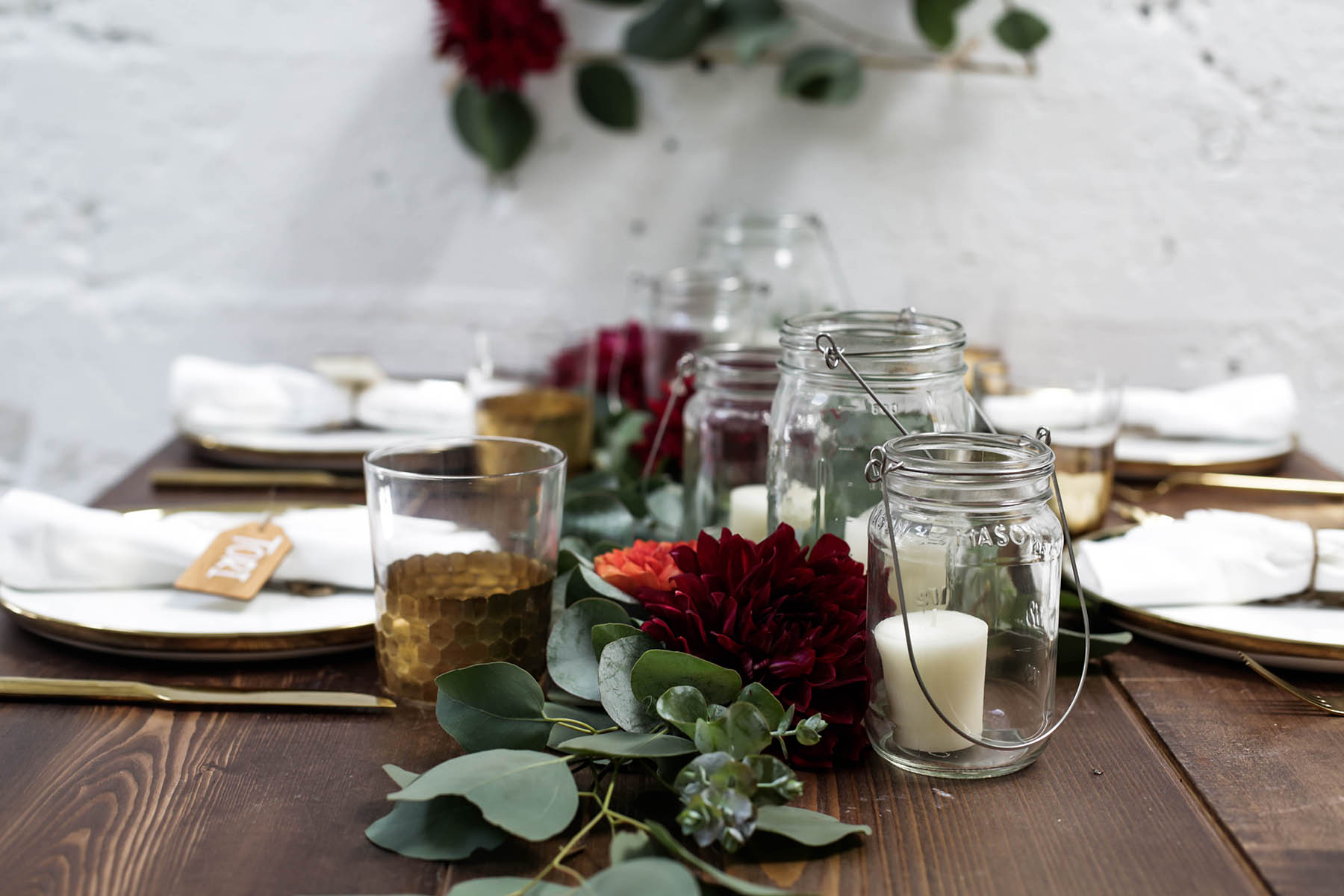 natural bohemian holiday tablescape centerpiece with candles, mason jars, florals and eucalyptus