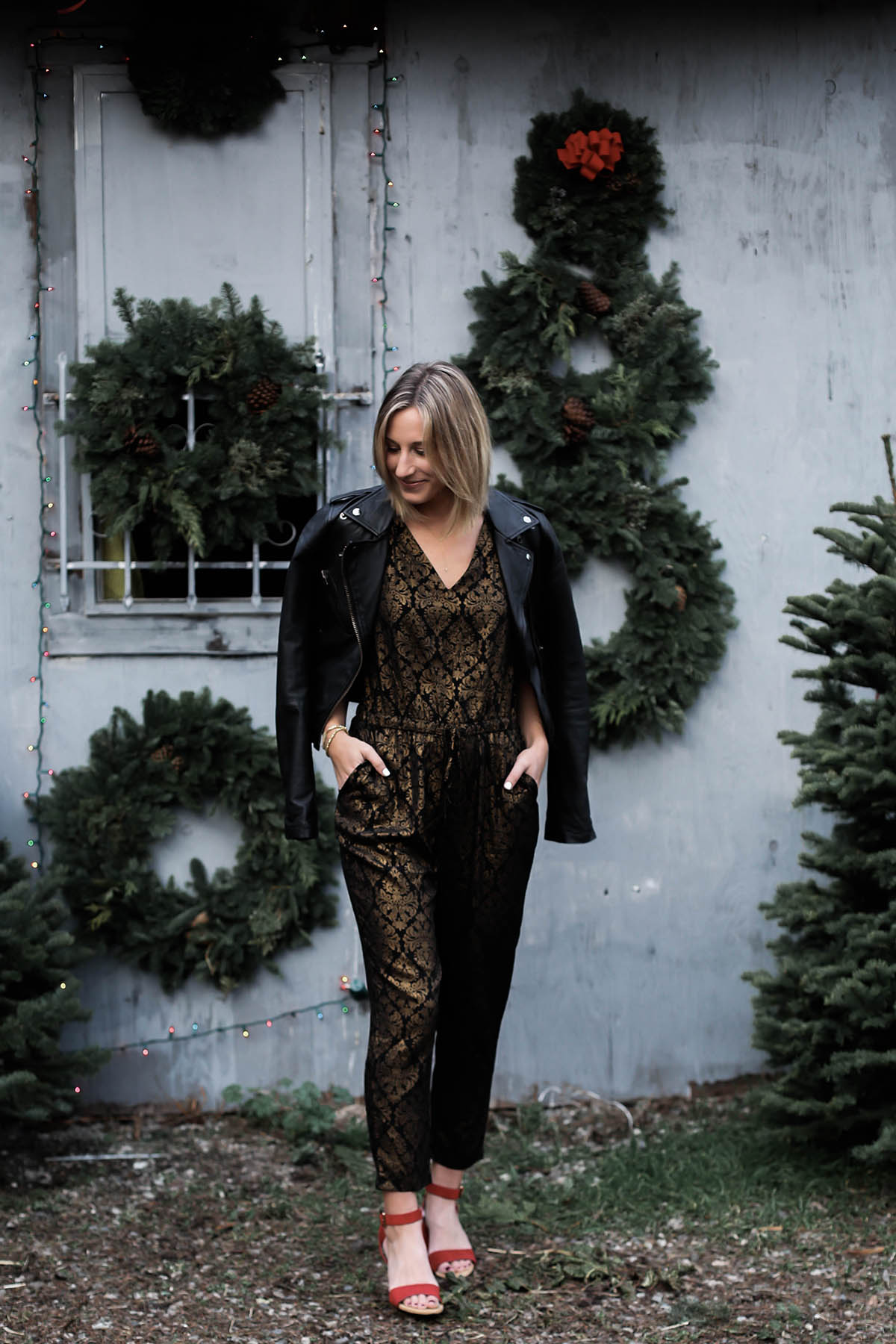 holiday jumpsuit and leather moto jacket and red shoes