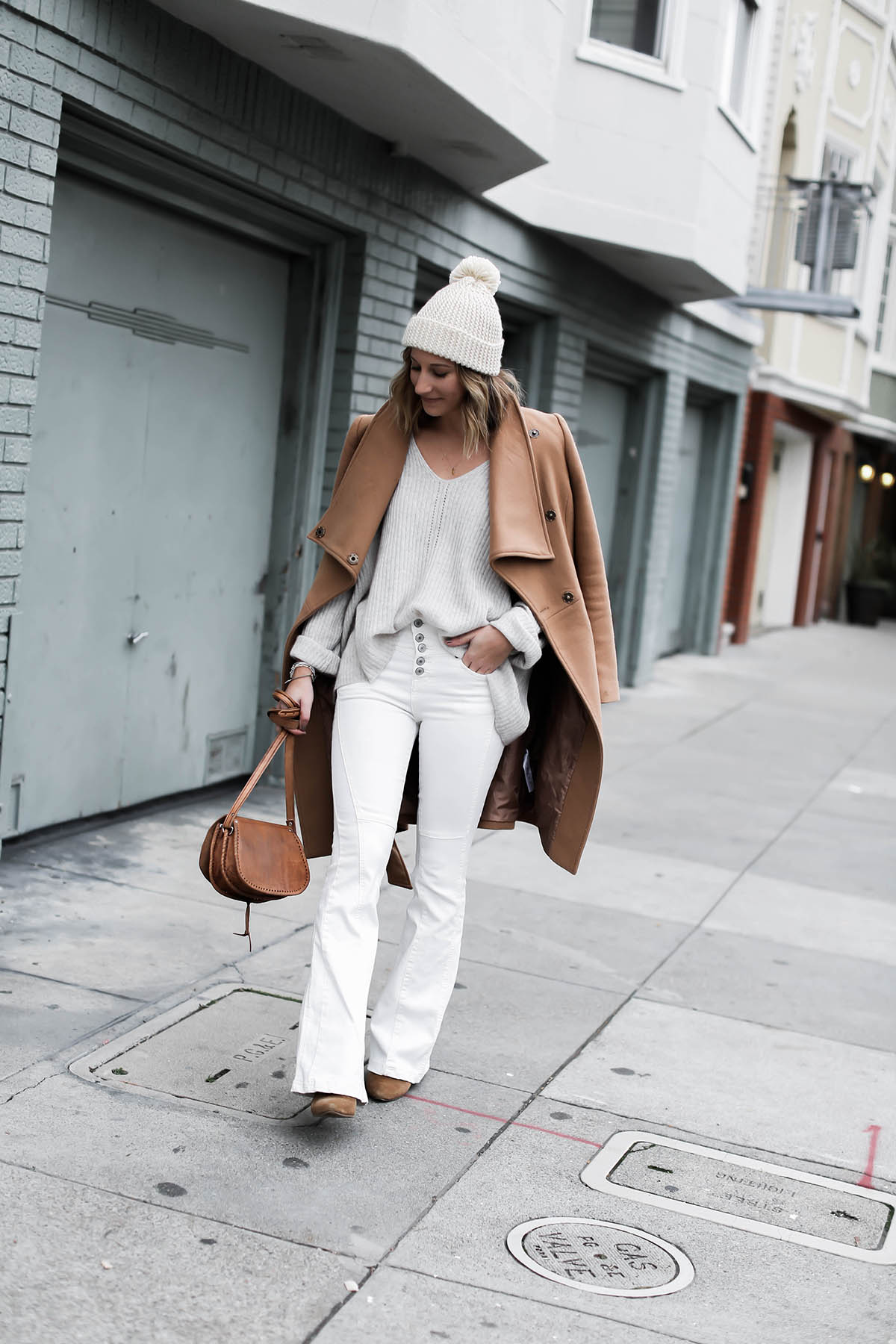 white flare jeans winter outfit with pom pom beanie and camel coat