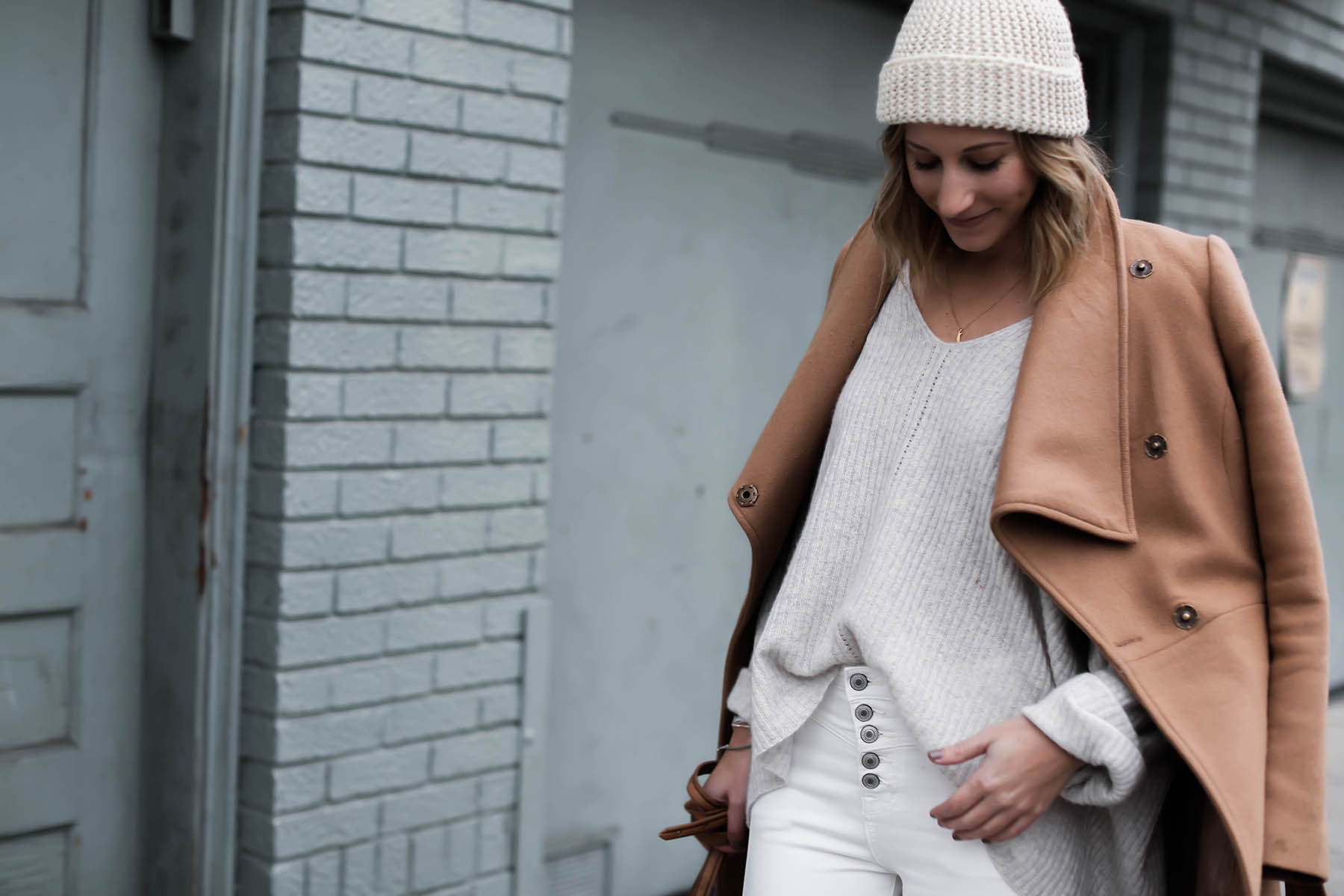winter white outfit with pom pom beanie and camel coat