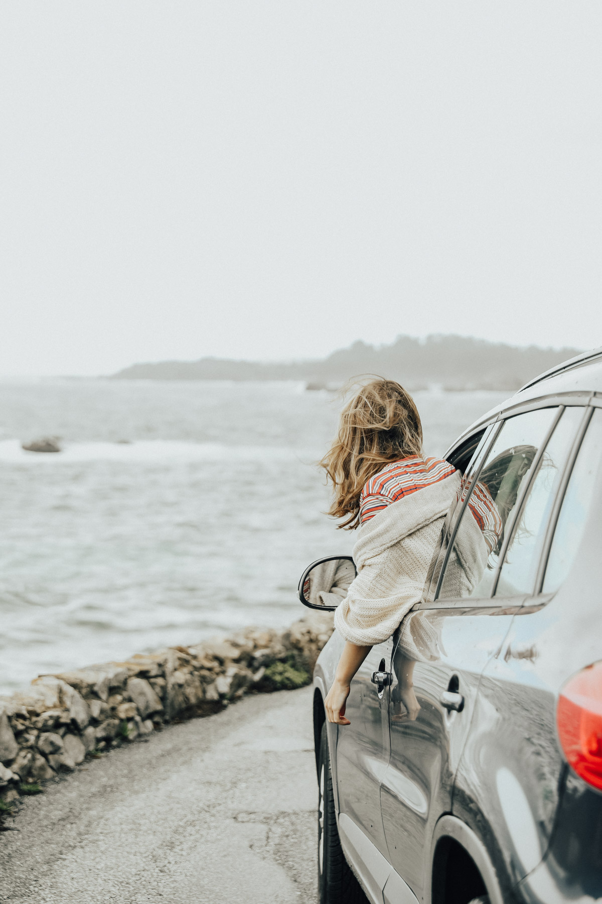 girl hanging out of car on road trip with view of pacific coast